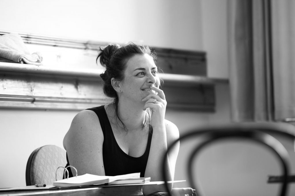 Black and white photograph of Julie Kelleher smiling looking ahead, off camera. She is mid directing a piece of theatre.